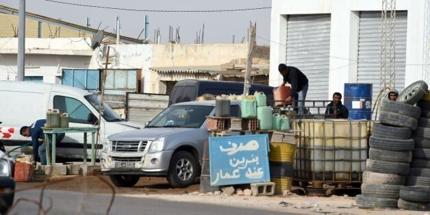 Tunisian smugglers unload barrels of oil, that they illegally imported from Libya to Tunisia, before...