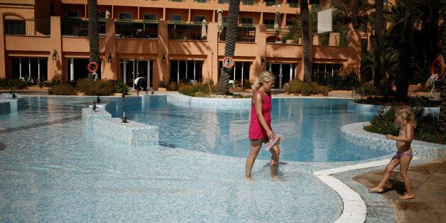 A Russian tourist walks in a swimming pool of El Ksar hotel in Sousse, Tunisia June 24, 2016. REUTERS/...