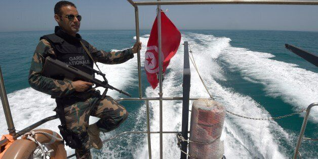 A member of the Tunisia's national guard patrols the sea bordering Tunisia and Libya for vessels potentially...