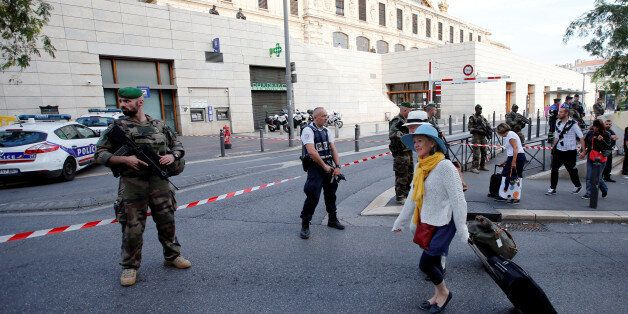 Travellers walk past French police and soldiers who secure a street near the Saint-Charles train station...