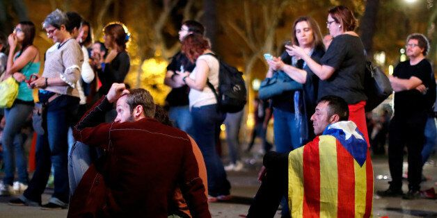 People react as they watch a session of the Catalonian regional parliament on a giant screen at a pro-independence...
