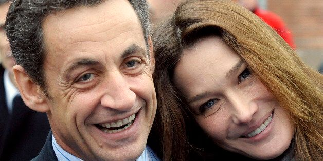 France's President Nicolas Sarkozy (L) and his wife Carla Bruni-Sarkozy pose before a visit a hospital...