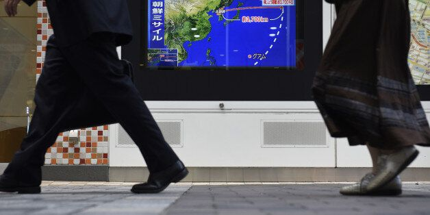 Pedestrians walk past a television screen displaying a map of Japan and the Korean Peninsula in a news...