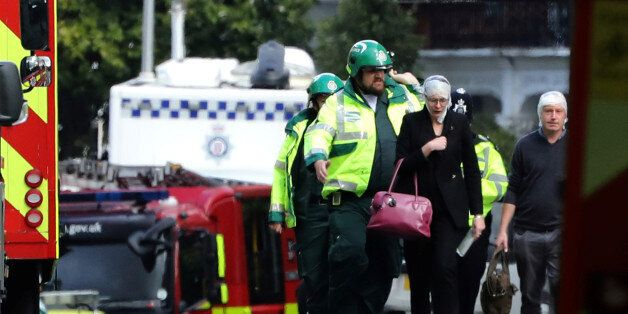 An injured woman is led away after an incident at Parsons Green underground station in London, Britain,...