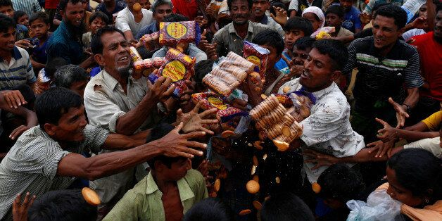 Rohingya refugees jostle to receive food distributed by local organizations in Kutupalong, Bangladesh,...