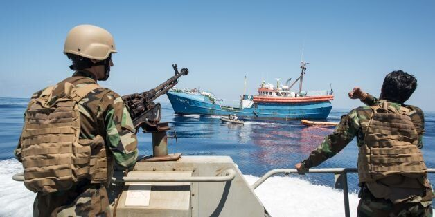 Libyan coastguards stand on an armoured boat as they patrol the area at sea between Sabratha and Zawiyah...