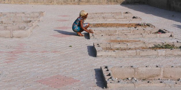A girl kneels near the graves of victims of a suicide bomb attack at St. Theresa's Church in Madalla,...