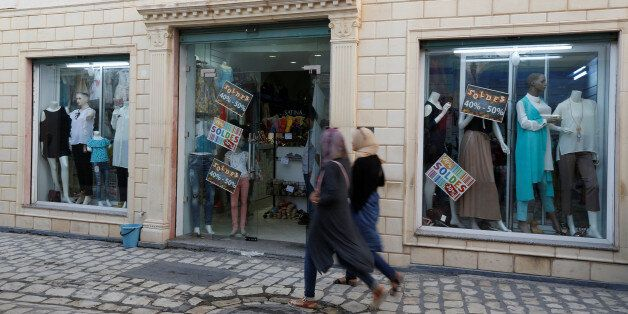 Women look at sale signs placed on a shop's windows while walking through central Mehdia,Tunisia, August...