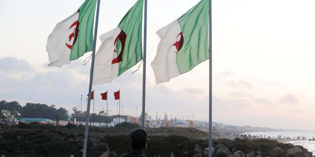 A soldier walks on the Algerian side of the Algeria-Morocco border as Algerian flags sway in the wind,...