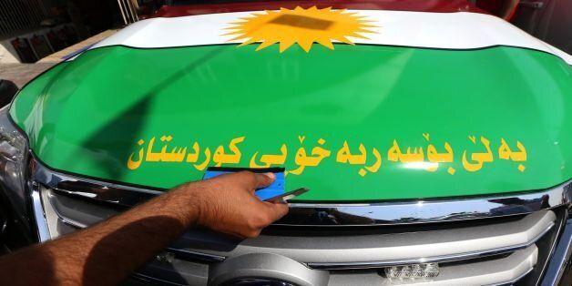 An Iraqi Kurdish man decorates a car with the Kurdish flags ahead of the upcoming independence referendum...