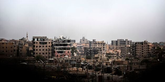 TOPSHOT - Damaged buildings are seen in western Raqa on July 12, 2017, during an offensive by Syrian...
