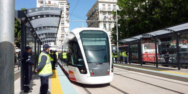 Algerian workers look at the tramway arriving at a tram stop on May 1, 2013 during the inauguration of...