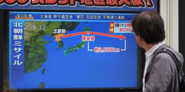 A pedestrian looks at a television screen displaying a map of Japan (R) and the Korean Peninsula in Tokyo...