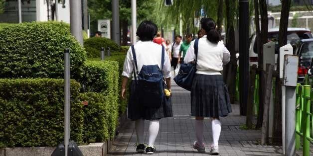 Japanese schoolgirls walk on a street in Tokyo on September 1, 2017.As Japan's schools reopened Friday...