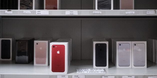 Boxes of Apple Inc. iPhone 7 smartphones sit at the storeroom inside an Orange SA mobile phone store...