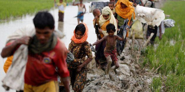 Rohingya refugees walk on the muddy path after crossing the Bangladesh-Myanmar border in Teknaf, Bangladesh,...