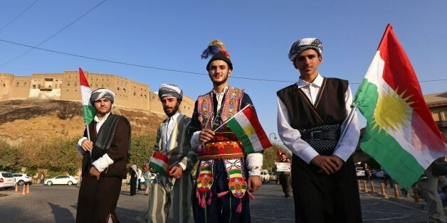 Iraqis dressed in traditional clothing and holding Kurdish flags walk near the citadel in Arbil, the...