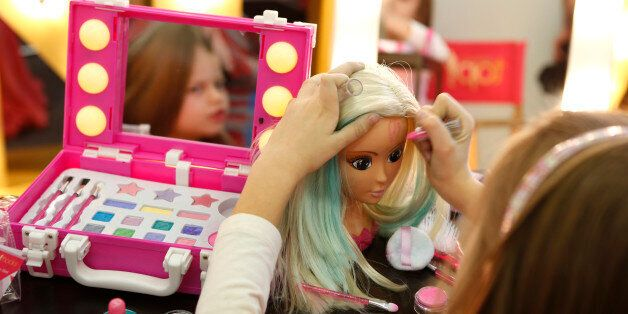 A young girl paints the face of a doll by the company Simba during the press preview of the 66th International...
