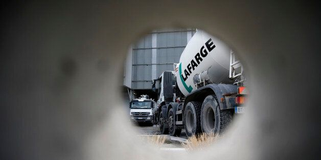 A concrete mixing truck is seen through a hole in a wall at Lafarge concrete production plant in Pantin,...