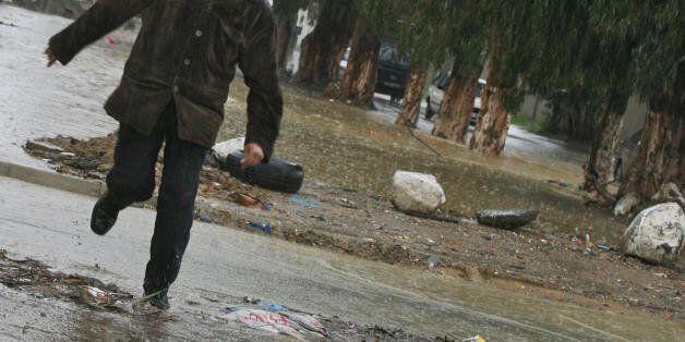 An Algerian man runs under a heavy rain in a street of Astawali, a western suburb of Algiers City 27...