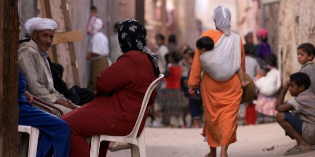 A Moroccan woman carries a young child in a sling on her back as shewalks along one of the many narrow...