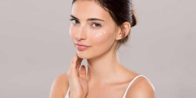 Young woman applying moisturizer on face isolated on grey background. Beautiful woman applying cosmetic...