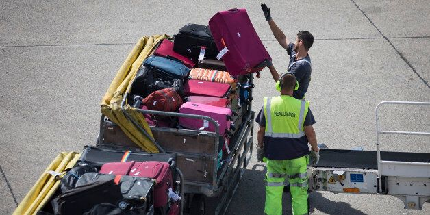 Airport staff unloads luggage from a plane at Tegel Airport on August 8, 2017 in Berlin. / AFP PHOTO...