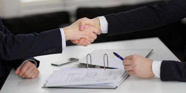 Berlin, Germany - March 23: In this Photo Illustration two people shaking hands on a table with documents...