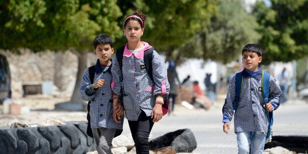 Tunisian school children walk past on April 14, 2016 a road block set up by residents of the island of...