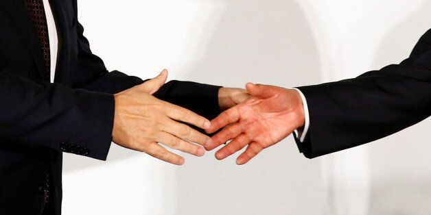 Carlos Ghosn (L), Chairman and CEO of the Renault-Nissan Alliance, reaches out to shake hands with Mitsubishi...