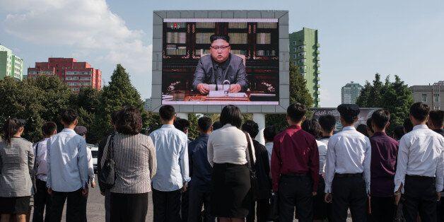 Des spectateurs écoutent un discours du leader nord-coréen Kim Jong-Un sur un écran public à Pyongyang,...