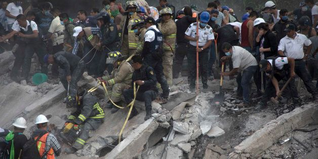 MEXICO CITY, MEXICO - SEPTEMBER 19: Rescuers and residents look for victims amid the ruins of a building...