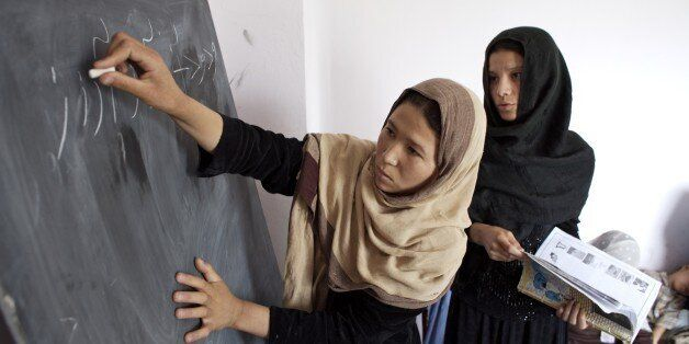 An Afghan woman writes Dari letters on blackboard with the help of the teacher, during an adult literacy...