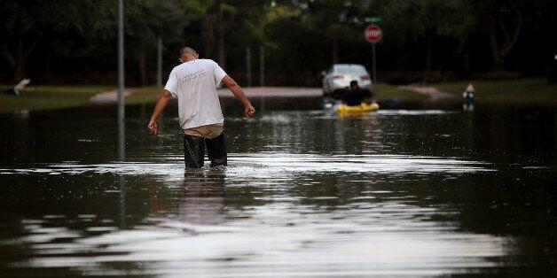 KATY, TX - SEPTEMBER 04: A man walks through a flooded street on September 4, 2017 in Katy, Texas. Over...