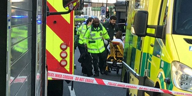Emergency personnel attend to a person after an incident at Parsons Green underground station in London,...