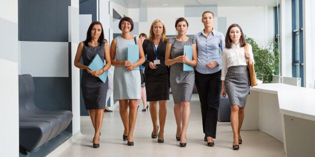 Group of confident businesswomen walking down the hall in modern