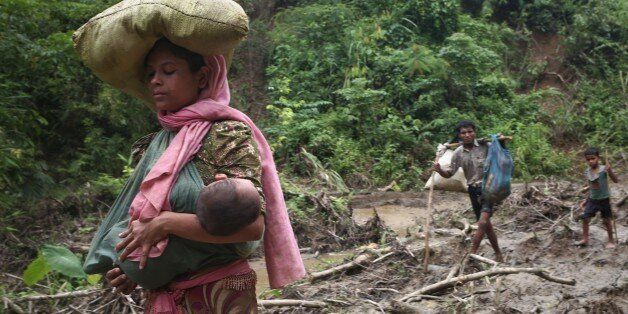 A rohingya woman carries her child in a sling while walks through in hill after crossing the border into...