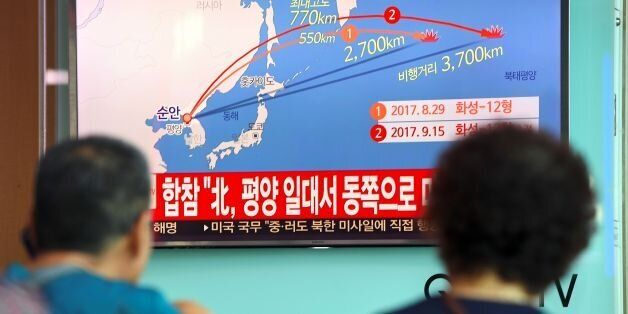 People watch a screen showing a graphic of a North Korean missile launch, at a railway station in Seoul...