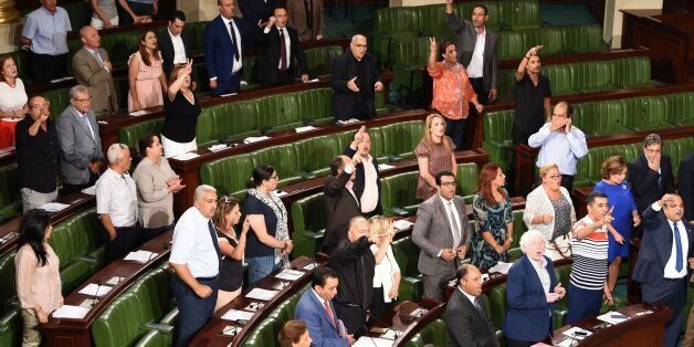 Members of Tunisia's Nidaa Tounes party celebrate after a contested reconciliation bill was adopted granting...
