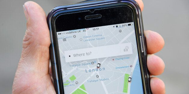 A photo illustration shows the Uber app on a mobile telephone, as it is held up for a posed photograph...