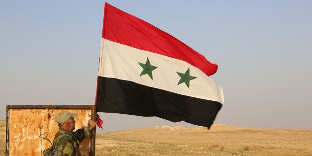 A member of the Syrian government forces stands next to a national flag as he secures a road for a military...