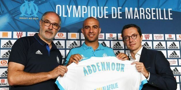Olympique de Marseille's newly recruited player, Tunisien defender Aymen Abdennour (C), holds his new...