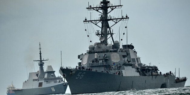 The guided-missile destroyer USS John S. McCain (R), with a hole on its portside after a collision with...