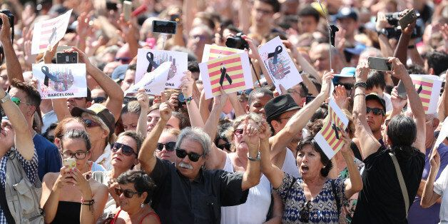 People hold banners as they observe a minute of silence in Placa de Catalunya, a day after a van crashed...
