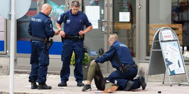 TOPSHOT - Police officers detain a suspect, in the Finnish city of Turku where several people were stabbed,...