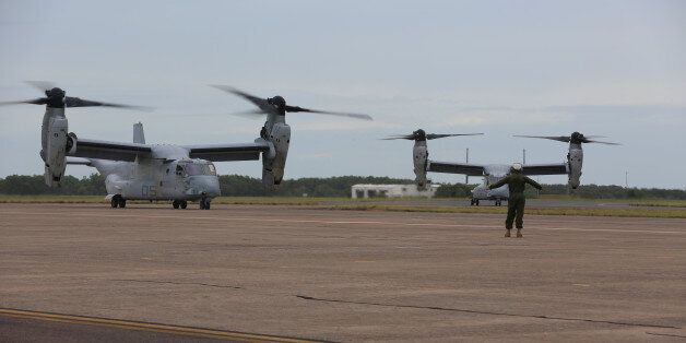 A U.S. Marine guides an MV-22B Osprey into position after the aircraft landed at Royal Australian Air...