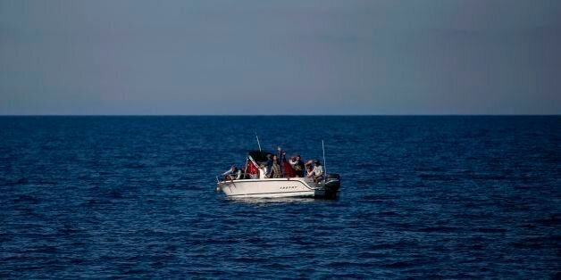 Migrants from Libya wave from a boat as they wait to be rescued by the Aquarius rescue ship run by NGO...