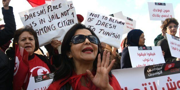 Tunisian women shout slogans during a demonstration outside parliament against allowing Tunisians who...