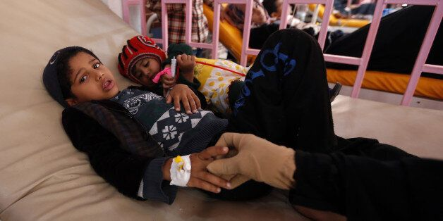 A Yemeni woman holds the hand of one of her children, who is suspected of being infected with cholera,...