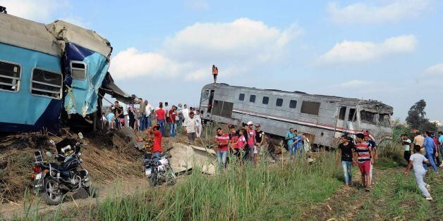 People gather at the site of a train collision in the area of Khorshid, in Egypt's Mediterranean city...